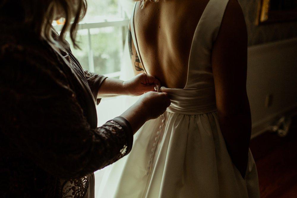 mother zipping bride in dress
