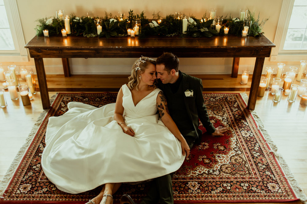 bride and groom portrait at altar with candles and rug