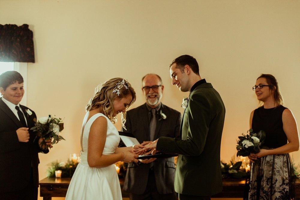 bride puts ring on groom's hand nashville wedding