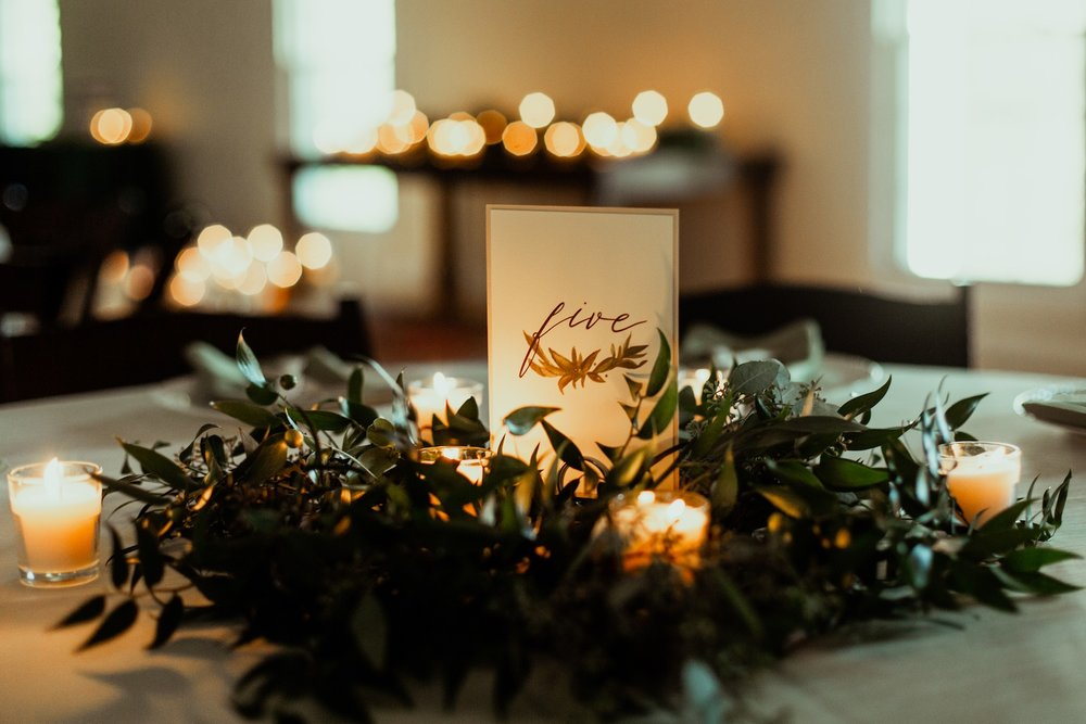wedding reception tablescape with greenery and candles