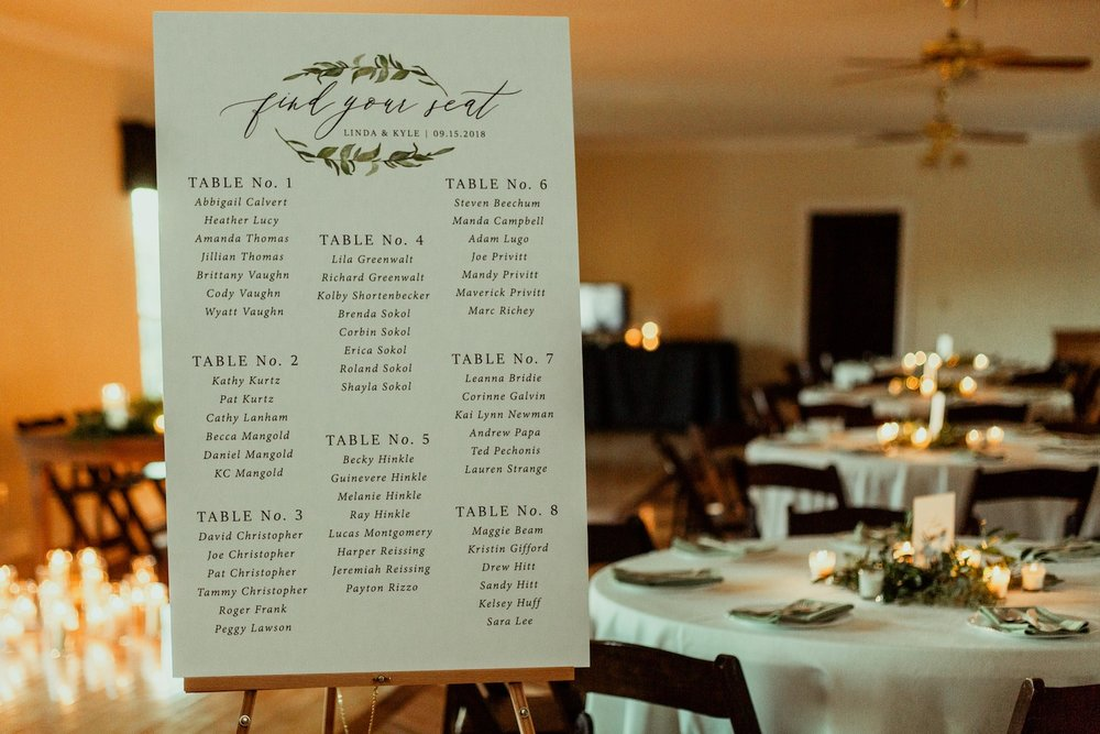reception seating chart with greenery and candles