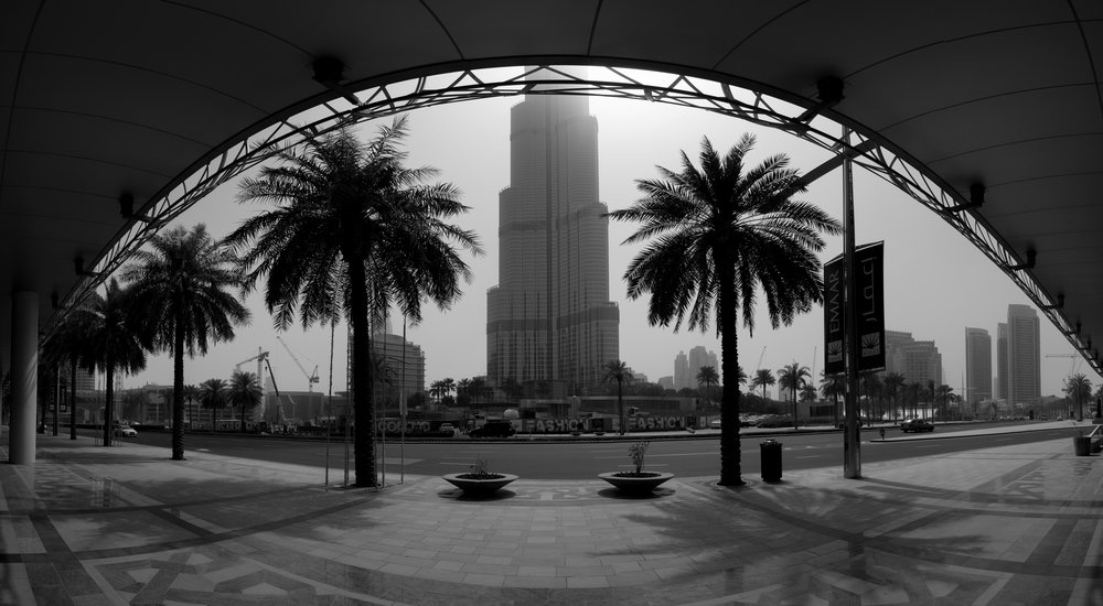 The glare of the sun peeking out around the Burj Khalifa, the tallest building in the world.