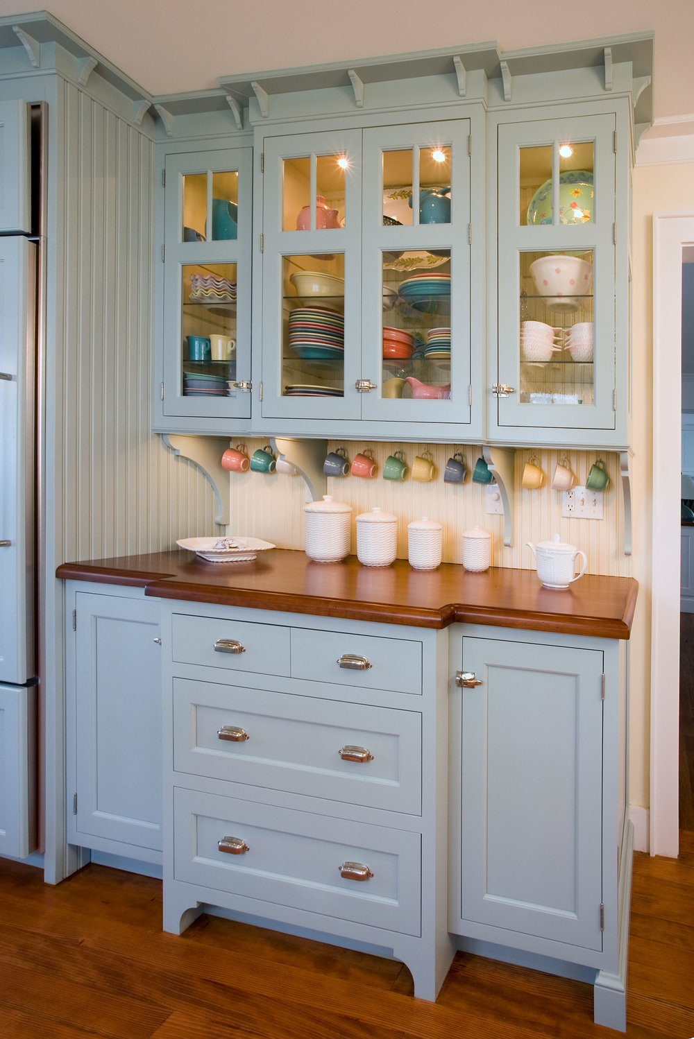 Storage - The hutch piece with a stepped out cherry countertop was created to showcase the owner's pastel Fiestaware collection. The wood top on the hutch also pulls in the tone of the floor.