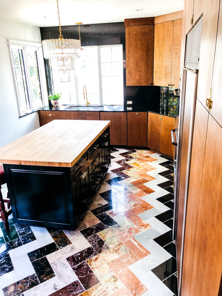 I am loving all this colored marble paired with flat panel wood cabinets that are a modern take on the midcentury cabinets of the past. The brass hardware is so warm and luxe and I'm just dying over the wall of black marble with white veins throughout.