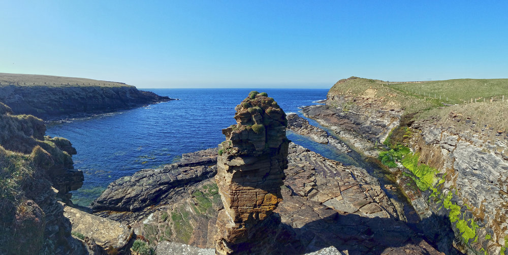 Borwick Castle sea stack at center, with the top of the Broch o' Borwick poking up at the top of the cliff at the top right.