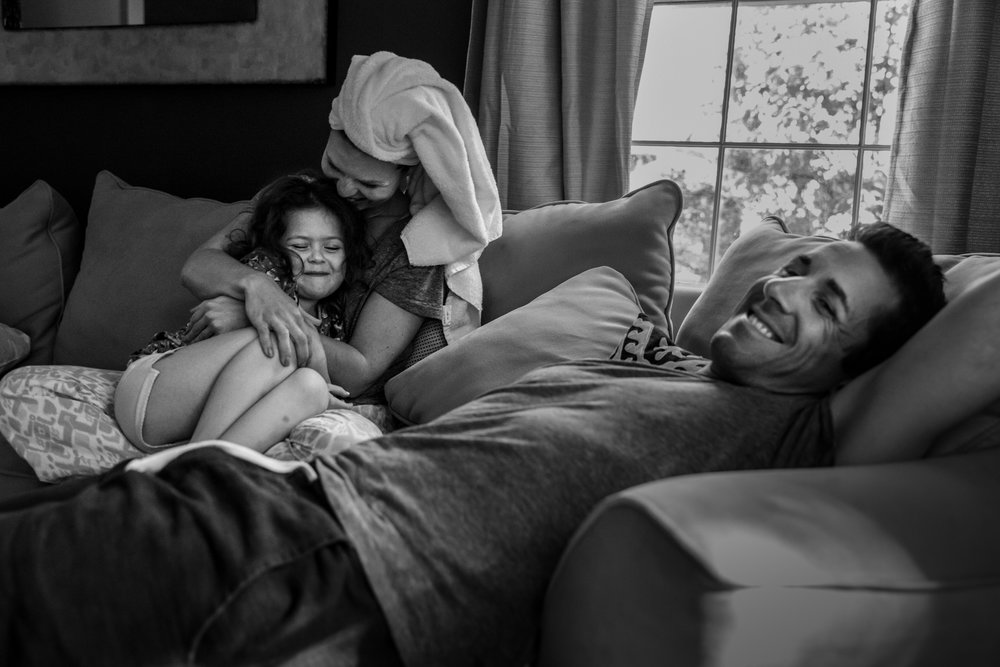 Mother and daughter snuggle while father smiles