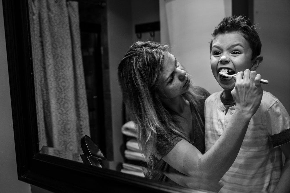 Woman brushes boy's teeth