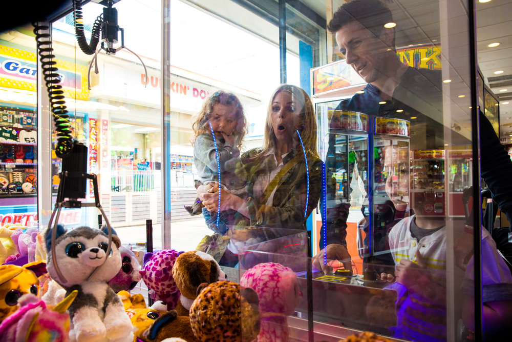Claw grabs prize at the arcade while family watches in suspense