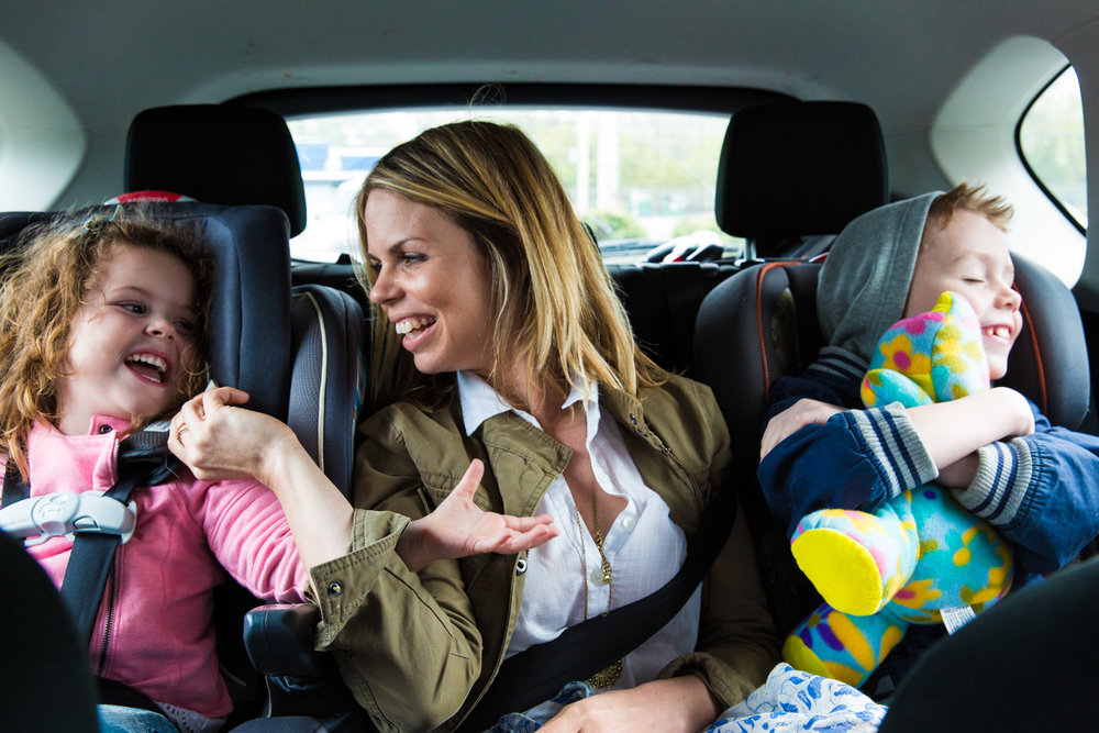 A Girl, a woman, and a boy ride in the back seat of the car with stuffed animals