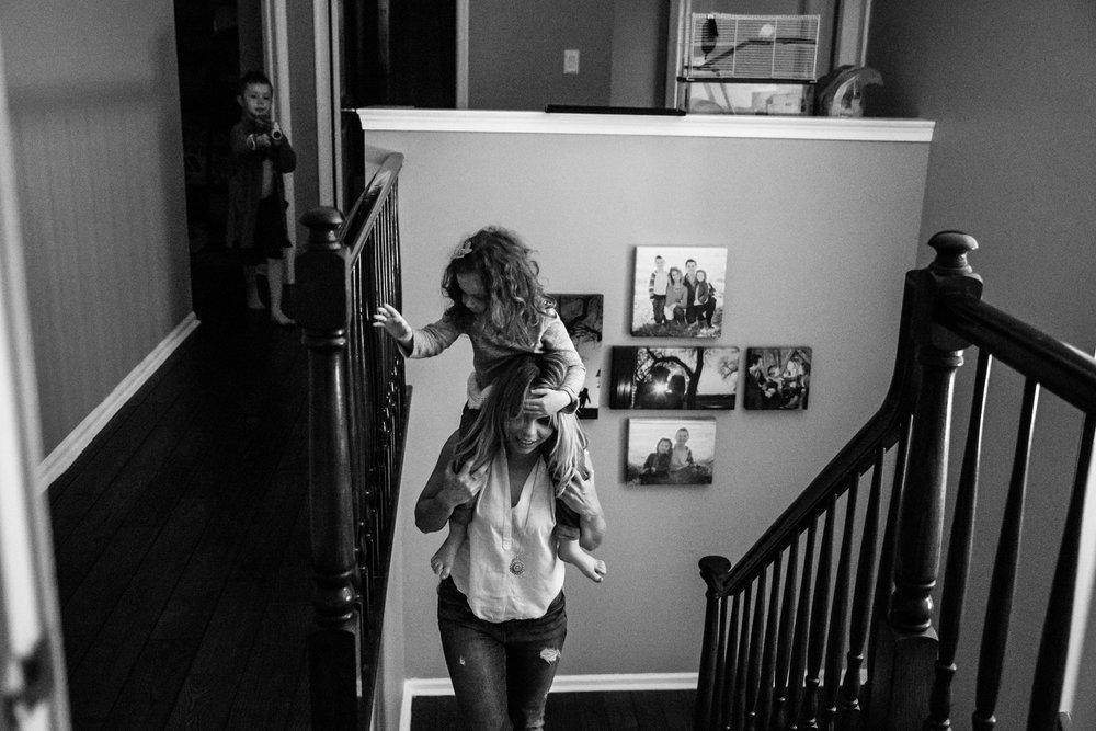 Girl rides on woman's shoulders while walking up the steps