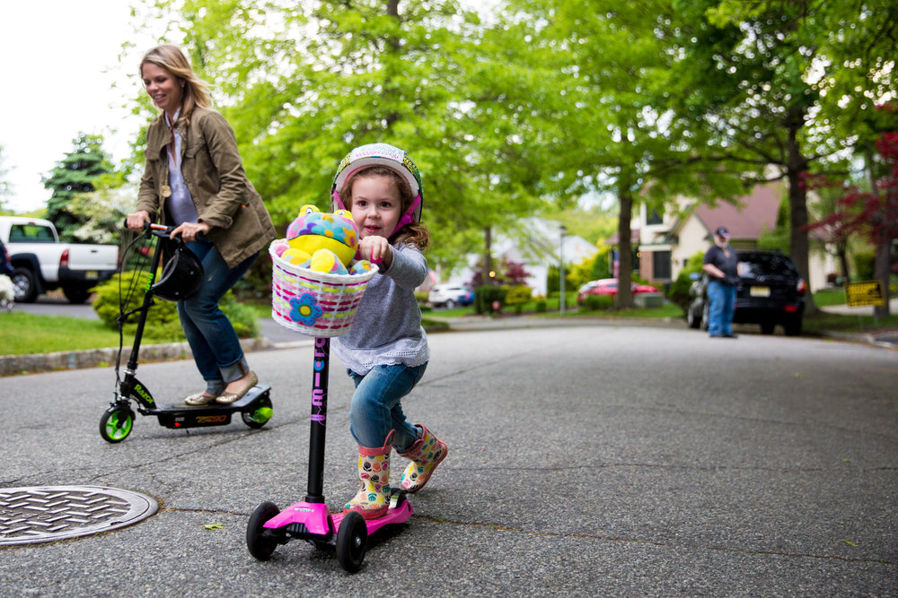 Woman and girl ride scooters on the street