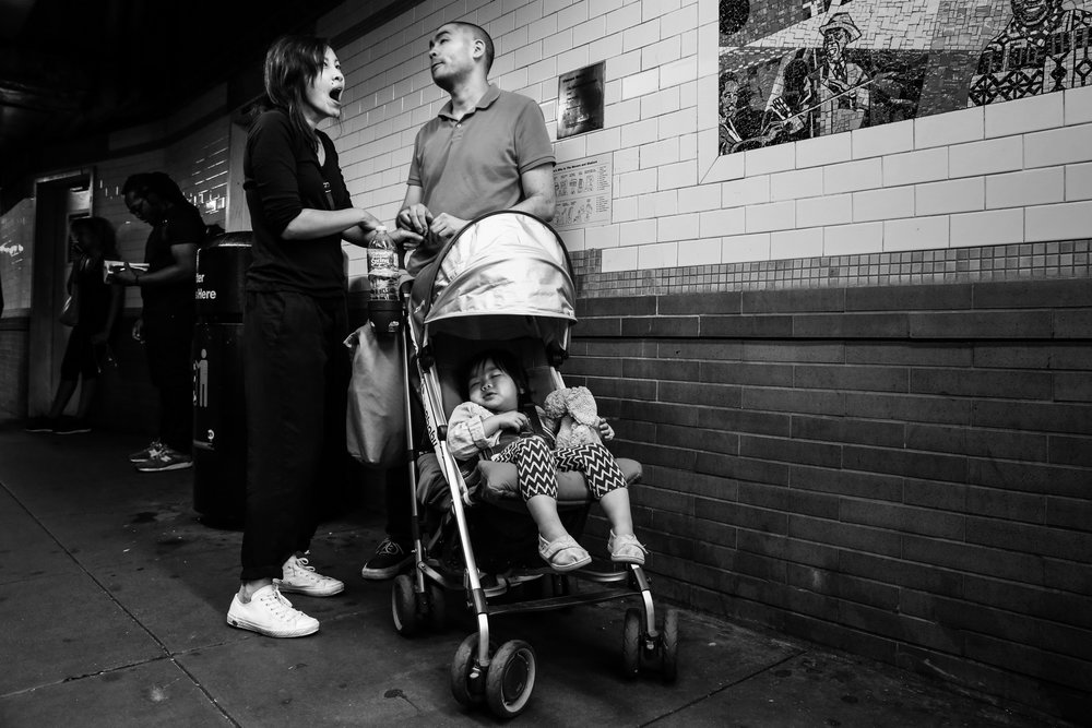Girl sleeps in stroller while man stands and woman yawns