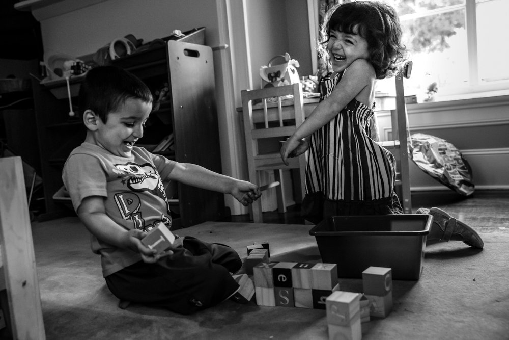 Boy knocks down toy blocks while girl laughs