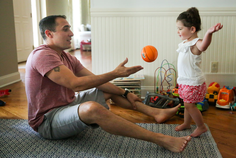 Man throws toy basketball to girl with outstretched arms