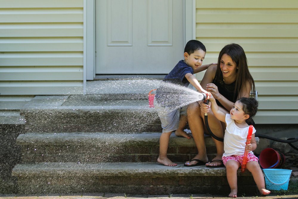 A boy and girl help their mom spray a garden hose while sitting on steps