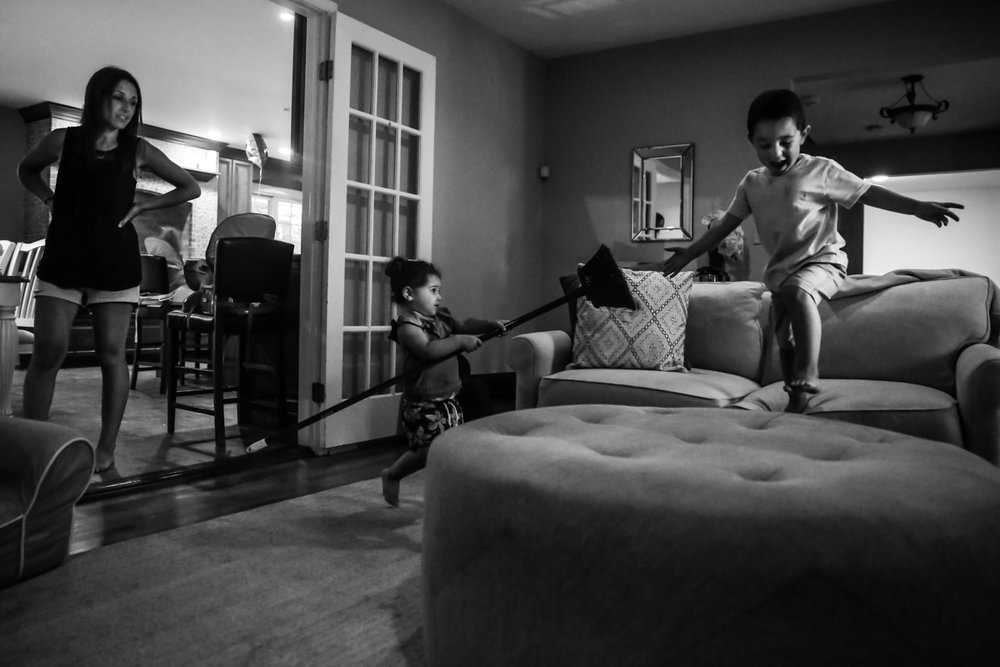 Boy jumps from couch to ottoman while girl chases him with a broom and woman watches from the side