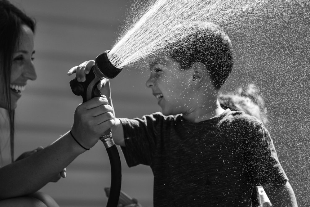 Mother and son smile at each other while spraying a garden hose