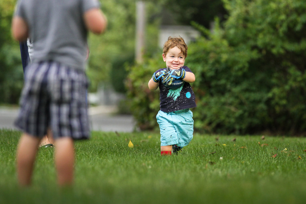 Boy wearing oversized gloves runs with football in grass