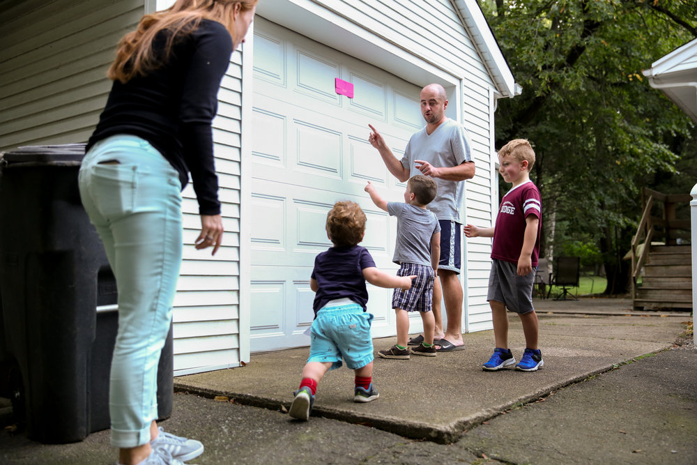 Man, woman, and three boys point to paper stuck up high on garage door
