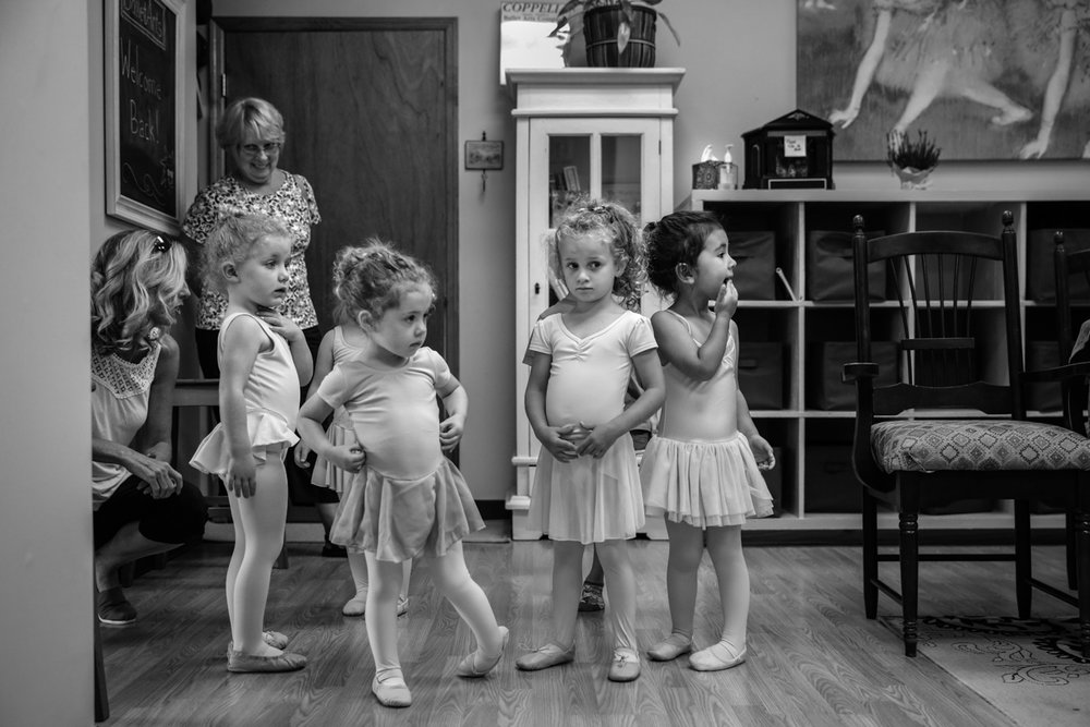Girls line up nervously in their ballet clothes before class