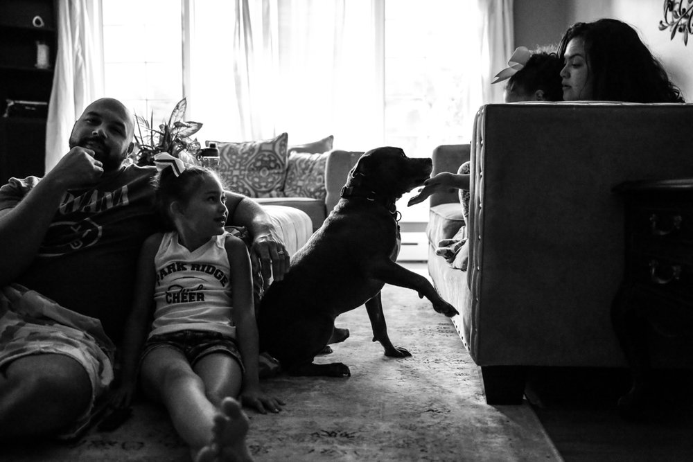 Family of four sit in living room with their dog