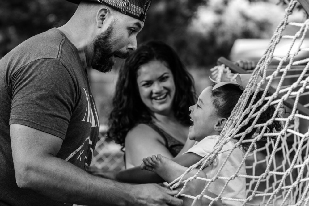 Man makes silly face while girl swings on hammock and woman watches smiling