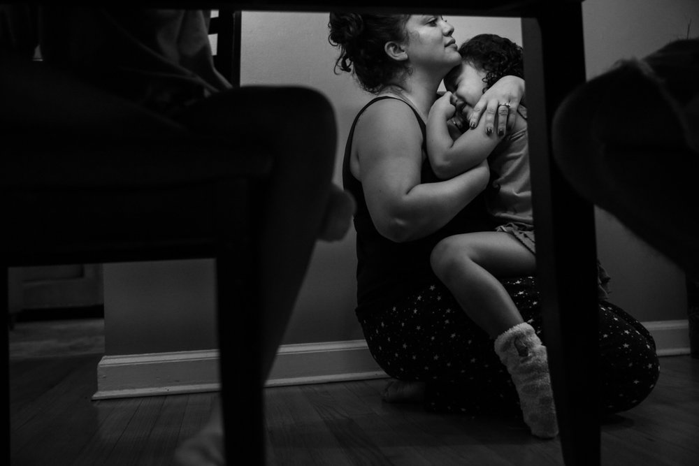 Woman holds crying girl on the floor