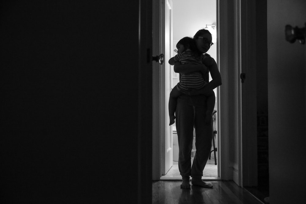 Mother carries daughter in hallway