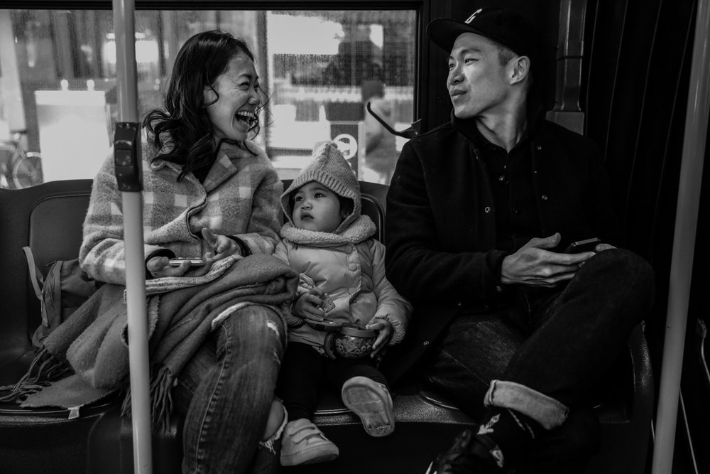 Man and woman smile at each other with girl in middle while sitting on the bus