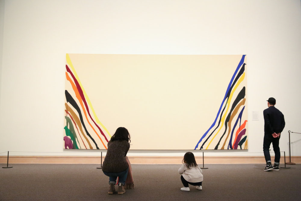 Man, woman and child look at Morris Louis painting