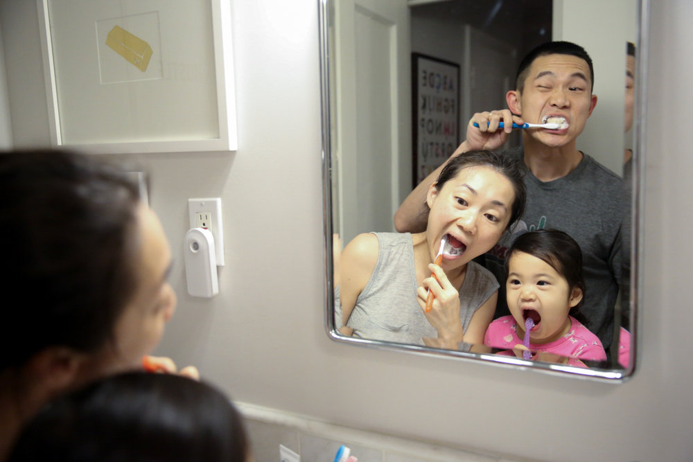 Man, woman, and child brush teeth together in the mirror