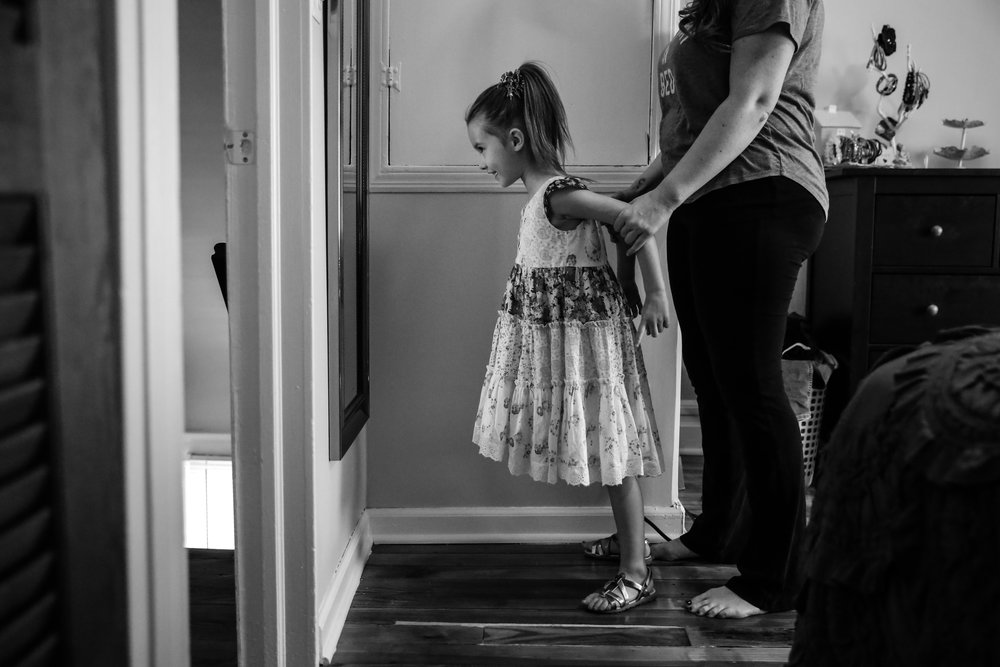 Girl stands in front of mirror reciting affirmations with mother