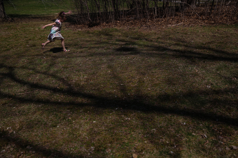 Girl frolics through tree shadowed lawn