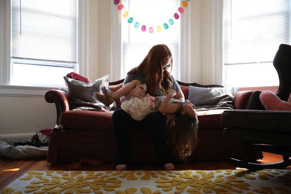 Woman holds girl in her arms while sitting on a couch