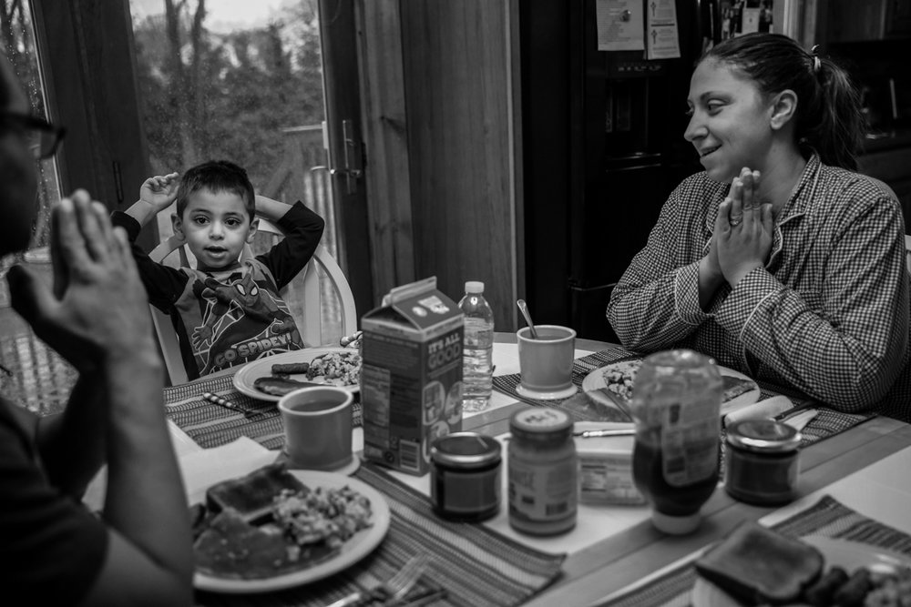 Family prays at table before breakfast