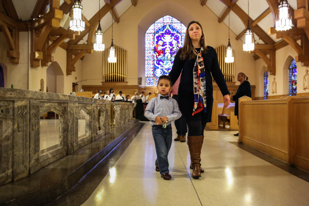 Woman and boy walk down aisle in church