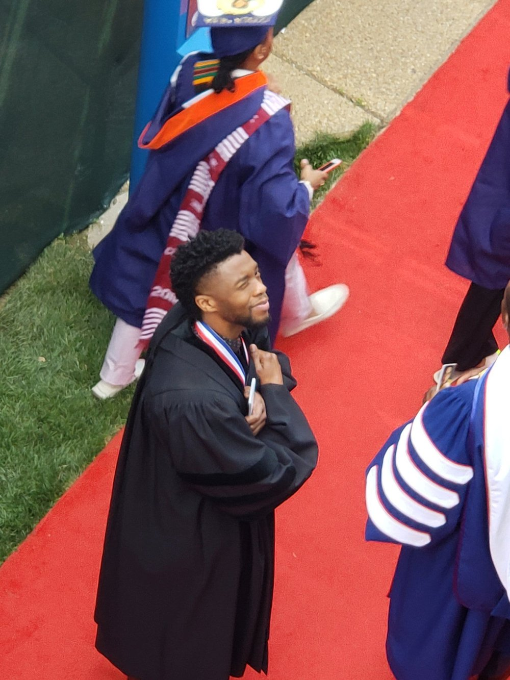 Chadwick Boseman, HU '00, entering 2018 commencement to receive his honorary doctorate. The Black Panther saluting. Wakanda Forever.