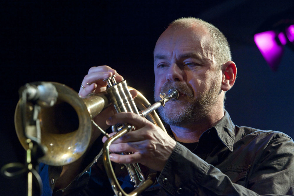 """""""Angelo Verploegen is een van de weinige trompettisten die de lager gestemde, loggere, maar ook kleurrijker intonerende bugel als eerste instrument heeft. -"""