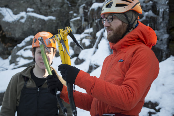 Aislinn Sarnacki |  BDN   Noah Kleiner (right), owner of Equinox Guiding Service, talks to his clients about the difference between ice axes on Dec. 20, while teaching them to ice climb in Camden Hills State Park.