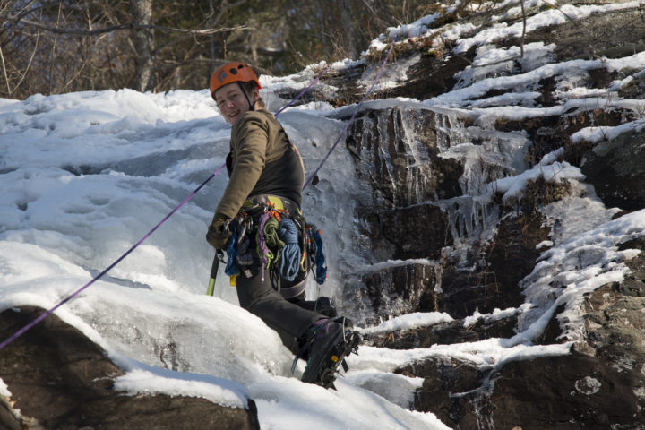 Aislinn Sarnacki |  BDN   Noah Rousseau, 13, of Appleton smiles while halfway up an ice route in Camden Hills State Park on Dec. 20, while learning to ice climb with Equinox Guiding Service.