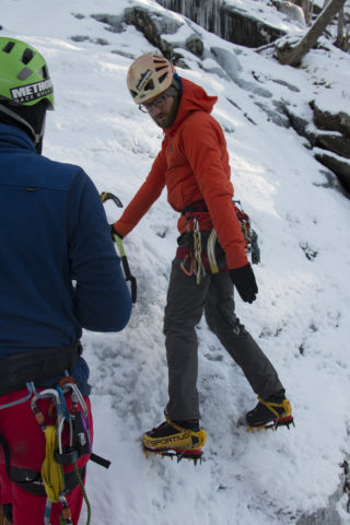 Aislinn Sarnacki | BDN  Noah Kleiner, owner of Equinox Guiding Service, demonstrates a wide stance while teaching beginners how to ice climb on Dec. 20 in Camden Hills State Park.