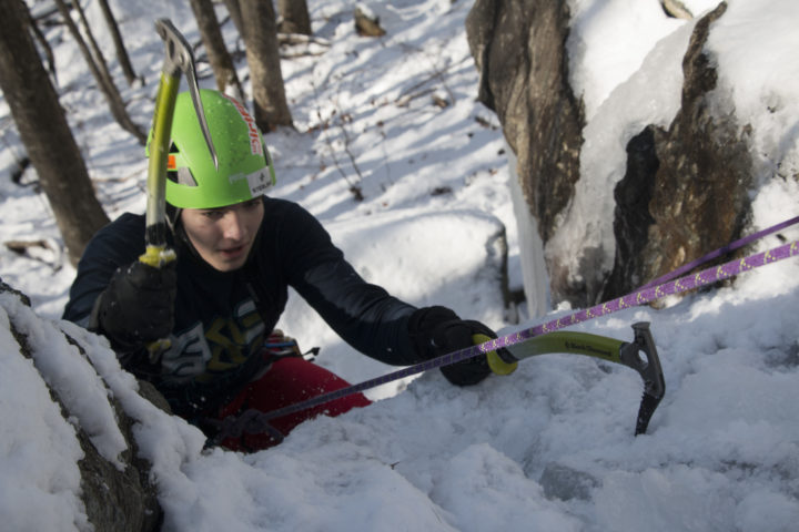 Aislinn Sarnacki |  BDN   Jack Main, 15, of Camden works his way over the lip of a wall of ice up Dec. 20 in Camden Hills State Park while learning to ice climb with Equinox Guiding Service.