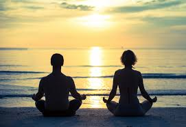 couple meditating on the beach.jpg