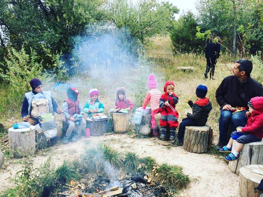 Wee Folk Forest Kindergarten Students Eat Snack Around the Campfire, Fall 2018