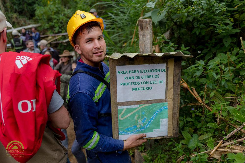 Alexandre, uno de los mineros de la mina Gualconda, muestra un anuncio que demuestra cómo predicen que la zona contaminada se verá después de la restauración.