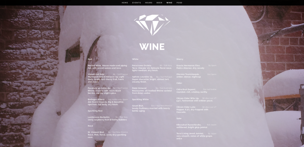 The wine menu with white text over a photo of beautiful, white snow.