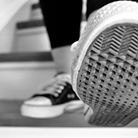 Photo: Two feet in sneakers, one taking a step off a stair.