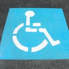 Photo: Blue and white wheelchair parking lot symbol painted on asphalt.