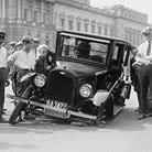 Photo: Old image of antique car with its front wheel having fallen off.