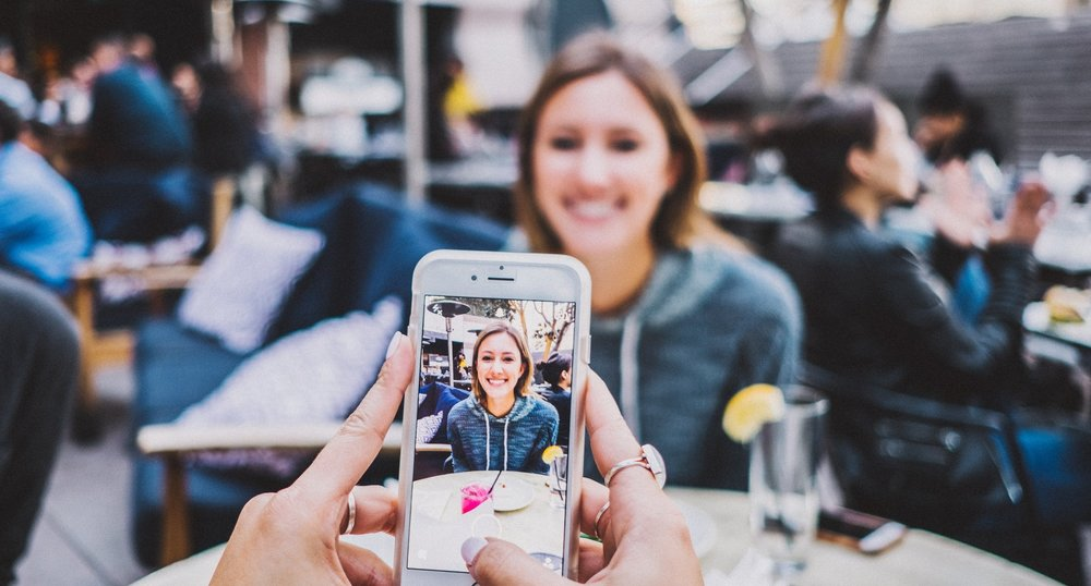 Photograph: Woman having her picture taken on a cellphone.